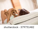 brunette is holding his puppy... | Shutterstock . vector #379751482