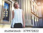 Small photo of Female student standing near University building while posing with laptop computer for magazine alumni, young woman entrepreneur standing near architectural monument after planing work on net-book