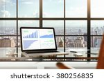 Financial statistics on laptop screen on glassy table in modern light office with megapolis city view - stock photo