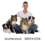 Stock photo four beautiful dogs and man in front of white background 380541556