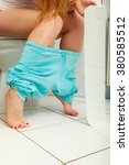 Small photo of Woman with constipation or diarrhoea sitting on toilet with her blue pajamas down around her legs, holding toilet paper ready in her hands