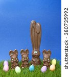 Small photo of Tall chocolate bunny with three short child sized bunnies on grass with easter eggs blue textured background. Copy space above