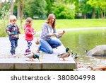 mother and her children feeding ... | Shutterstock . vector #380804998