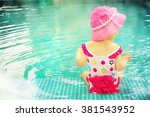 baby sitting near swimming pool. | Shutterstock . vector #381543952