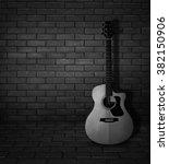 Small photo of Acoustic guitar lay on the brick wall - black and white pic