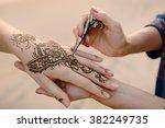 Artist Applying Henna Tattoo O...