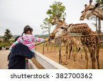 mother and girl at public zoo  | Shutterstock . vector #382700362