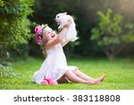 Stock photo girl playing with real rabbit in sunny garden child and bunny on easter egg hunt in flower meadow 383118808