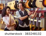 Small photo of Beautiful Afro-American girl and handsome man choosing a guitar and smiling while standing in a musical shop