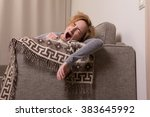 yawing girl lie on brown sofa | Shutterstock . vector #383645992