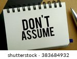 Small photo of Don't assume memo written on a notebook with pen