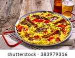 Small photo of Wholesome Spanish al homo paella with black pudding and grilled spare ribs served on a bed of savory saffron rice with herbs and red bell peppers