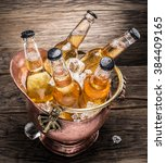Small photo of Cold bottles of beer in the brazen bucket on the wooden table.