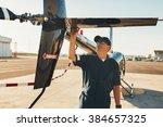 Male Pilot In Uniform Examining ...