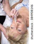 Small photo of Nurse administering nasal drops into a patients nose
