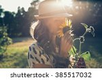 girl smells sunflower in nature | Shutterstock . vector #385517032