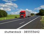 Red Truck Driving On Asphalt...