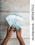 handing out money in malaysia... | Shutterstock . vector #385567012