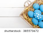 blue easter eggs in a basket on ... | Shutterstock . vector #385573672