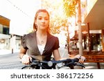 young woman commuting on bicycle | Shutterstock . vector #386172256