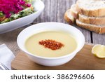 Small photo of Mercimek Corba is traditional Turkish lentil soup with salad and bread slice on wooden background