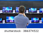 man looks at lcd tvs in... | Shutterstock . vector #386374522