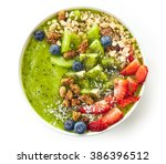 Small photo of breakfast kiwi smoothie bowl topped with oat flakes and berries isolated on white background, top view