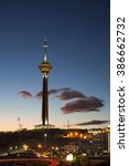 Small photo of Illuminated Milad Tower in the Skyline of Tehran at Dusk Against Cloudy Blue Sky.