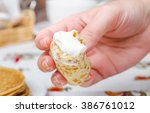 the hand holds a rolled pancake ... | Shutterstock . vector #386761012