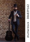 Small photo of Stylish young bearded man in gibus and sunglasses is leaning on a guitar and posing while standing against brick wall