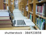 Small photo of note book open with books addle in library room