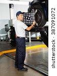Small photo of Mechanic Adjusting Wheel Alignment Machine
