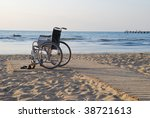 Wheelchair on sandy seacoast. - stock photo