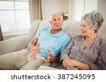 senior couple sitting on sofa... | Shutterstock . vector #387245095