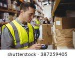 warehouse worker scanning box... | Shutterstock . vector #387259405