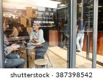 Stock photo woman with friends at a cafe seen through window 387398542