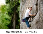 A female climber, climbing using a top rope on a steep rock face (crag) - stock photo