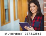 smiling student using tablet in ... | Shutterstock . vector #387513568