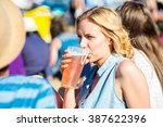 young blond woman with beer at... | Shutterstock . vector #387622396
