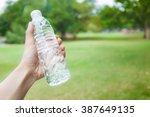 hand holding fresh water bottle ... | Shutterstock . vector #387649135