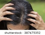young woman shows her gray hair ... | Shutterstock . vector #387675352