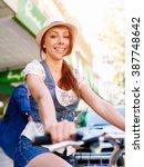 beautiful woman riding on bike | Shutterstock . vector #387748642