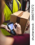 Small photo of Woman signing on device to delivery parcel by van