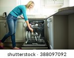 pretty blonde woman emptying... | Shutterstock . vector #388097092