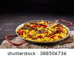 Small photo of Rustic metal dish of delicious traditional Spanish paella al homo with black pudding and spare ribs on yellow saffron rice with red sweet peppers, with copy space