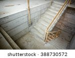 Small photo of New concrete staircase with temporary wooden handrail, under construction.