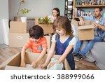 family unpacking cardboard... | Shutterstock . vector #388999066