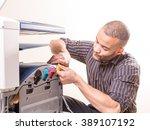 african man fixing photo copier   Shutterstock . vector #389107192