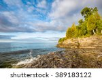 A small wave breaks and splashes under a cloudy blue sky at Door County, Wisconsin