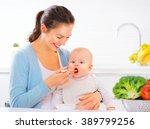 mother feeding her baby girl... | Shutterstock . vector #389799256